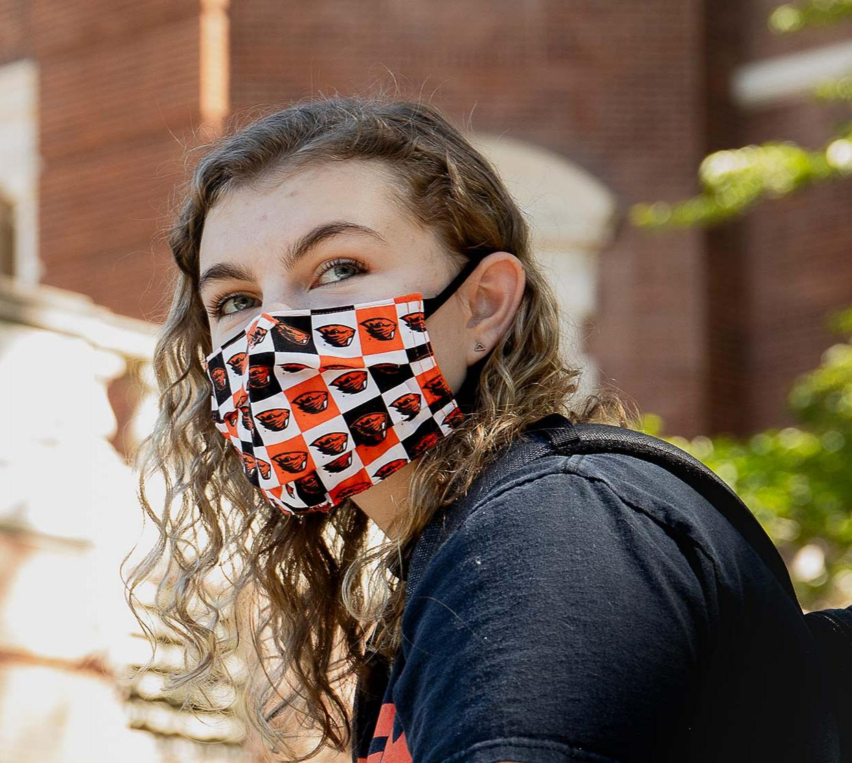 OSU student wearing a mask in front of Weatherford Hall.