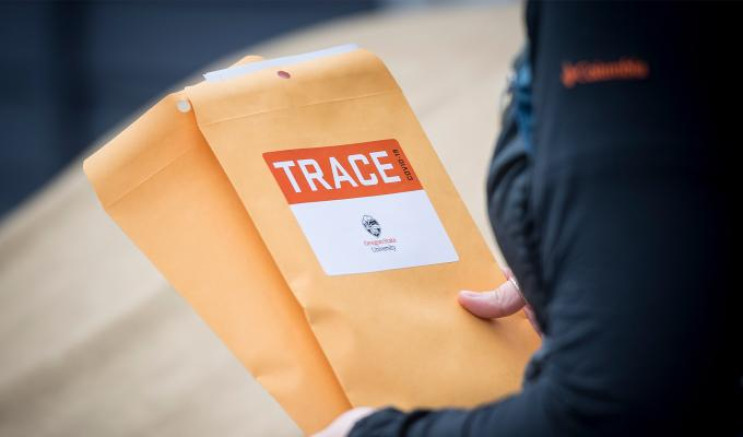 TRACE field staff member holding manilla envelopes with TRACE stickers on them.