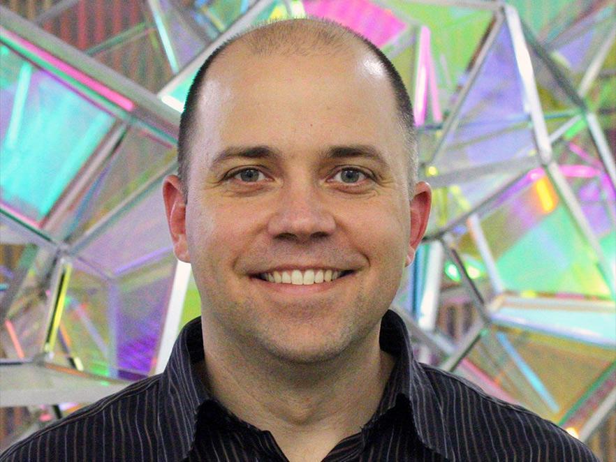 Tyler Radniecki standing in front of glass sculpture.